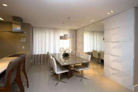 55. Sala com parede com revestimento de gesso 3D e espelho grande. Projeto de Marina Turnes
