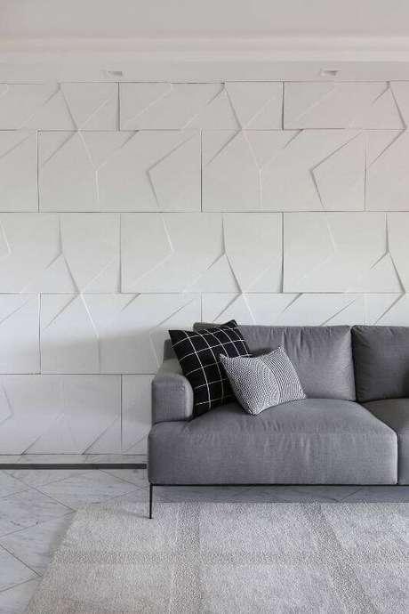 56. Sala moderna com parede com gesso 3D atrás do sofá cinza. Projeto de Bianchi Lima