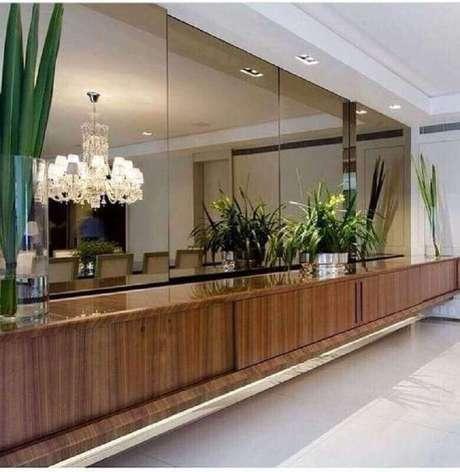 16. Buffet de madeira decorado com vasos de plantas e espelho bronze – Foto: Pinterest