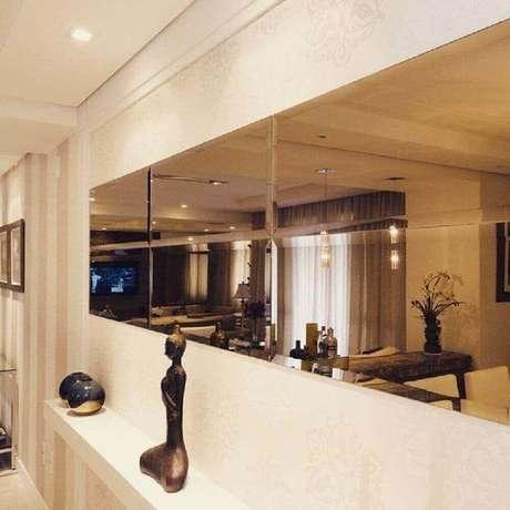 18. Corredor decorado com espelho de bronze e pequena bancada branca – Foto: Elaine Castanheira Arquiteta