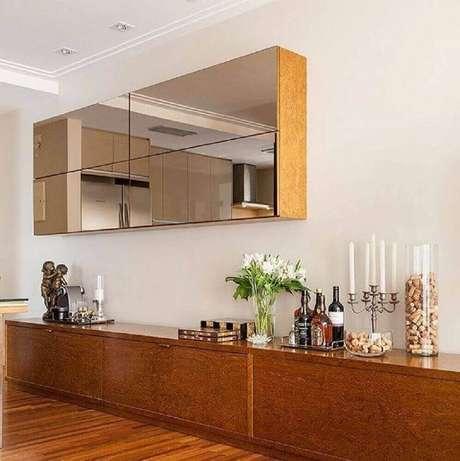 22. Decoração com buffet de madeira e armário aéreo espelhado bronze – Foto: Estúdio AE