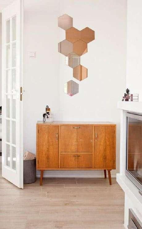 23. Buffet de madeira decorado com vários espelhos de bronze e prata em formato de hexágono – Foto: Moody's Home