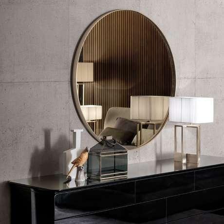 1. Decoração com espelho de bronze redondo sobre aparador preto – Foto: Pinterest
