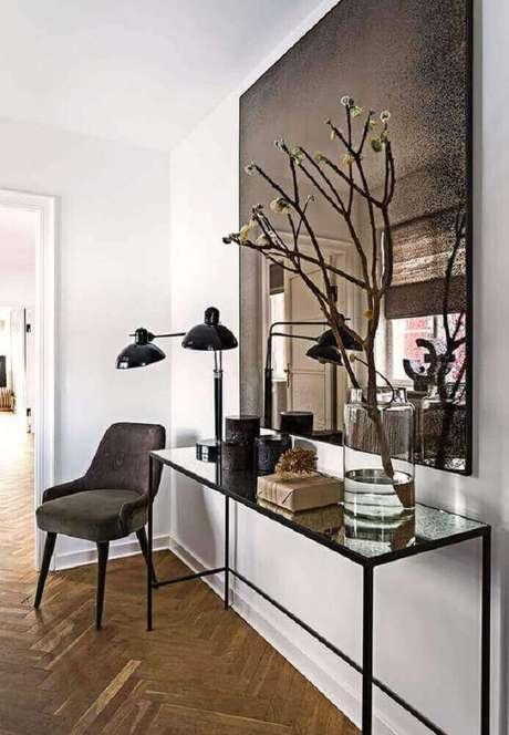26. Decoração com grande espelho de bronze quadrado e luminária preta sobre aparador minimalista – Foto: HomeDeco