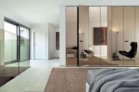 42. O quarto amplo também pode ter um guarda roupa espelho bronze – Foto: Studio Invita