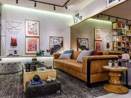 50. O espelho bronze deu um toque diferente na sala de estar com puff redondo capitonê e sofá de couro – Foto: Pinterest