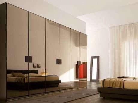 7. Decoração para quarto com guarda roupa espelho bronze – Foto: David Lang