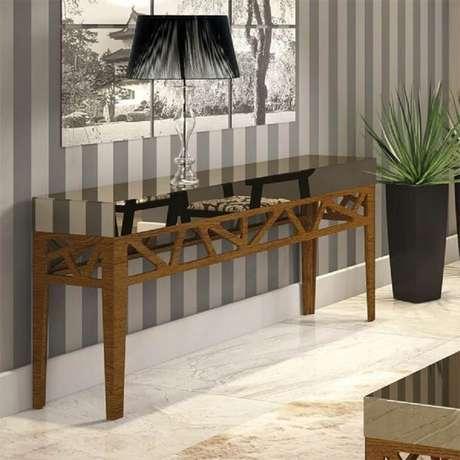 5. Decoração com papel de parede listrado e aparador espelhado bronze com pernas de madeira – Foto: Pinterest