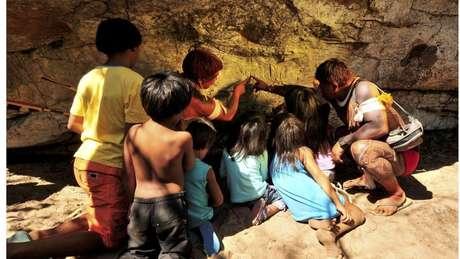 Um índio Waurá ensinando a mitologia em torno do guerreiro Kamukuwaká a crianças da aldeia usando as gravuras da caverna no Xingu antes do local ser vandalizado