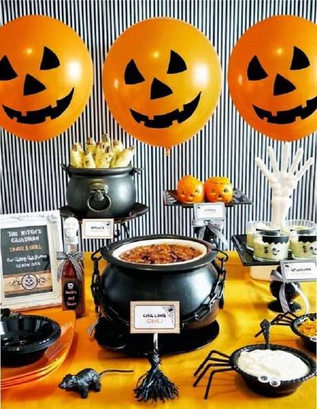 35. Decoração para festa de Halloween com caldeirão de ferro e balões laranjas – Foto: Woodland Springs