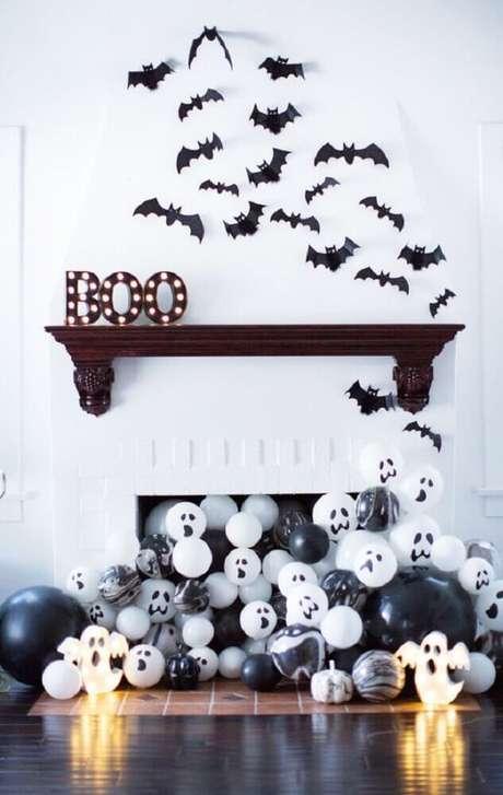 6. Linda decoração de Halloween com muitos balões saindo da lareira e morcegos na parede – Foto: MOODecor
