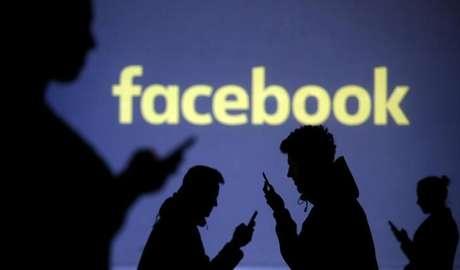 Pessoas utilizam celulares diante de projeção do logo do Facebook em foto ilustrativa 28/03/2018  REUTERS/Dado Ruvic/Illustration