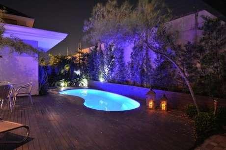 23. Área externa com piscina pequena iluminada e deck de madeira. Projeto de Paulinho Peres
