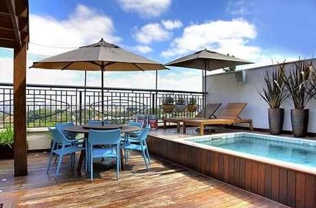 27. Deck de piscina pequena e espreguiçadeiras e mesa com ombrelone. Projeto de Studio Scatena