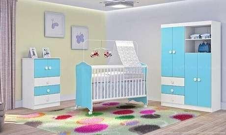 51- No quarto de bebê menino as portas dos móveis são azuis e o tapete tem estampa com círculos coloridos grandes. Fonte: LojasKD
