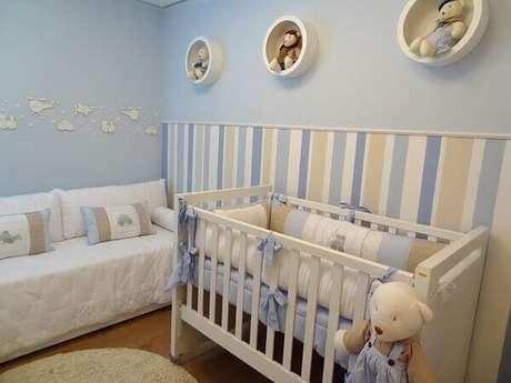 30- Na parte inferior da parede foi utilizado papel de parede listrado e na parte superior pintada de azul foram colocados três nichos redondos na cor branca. Projeto: Grazi Ela