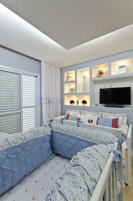 57- O painel com nichos iluminados e tv decoram o quarto de bebê masculino simples. Projeto: Belissa Corral