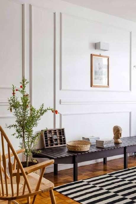 14. Decoração com tapete listrado, cadeira de madeira e parede com boiserie gesso – Foto: The Holk