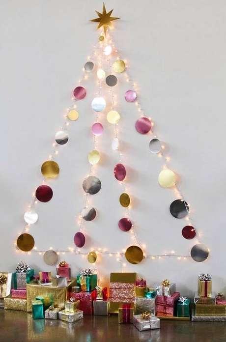 17. Árvore artesanal super fofa feita direto na parede só com um pisca-pisca e papéis coloridos