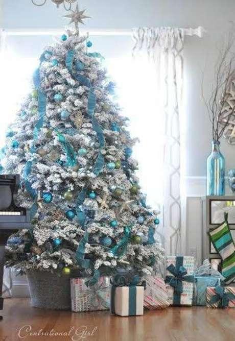 64. Árvore de natal coberta de neve artificial e enfeitada com bolas azuis e fitas
