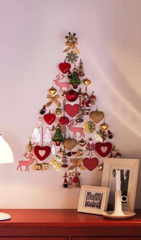 23. Árvore natalina feita na parede com adesivos e enfeites de natal