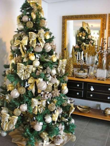 32. Árvore de natal glamourosa com enfeites dourados e laços com estampa de oncinha