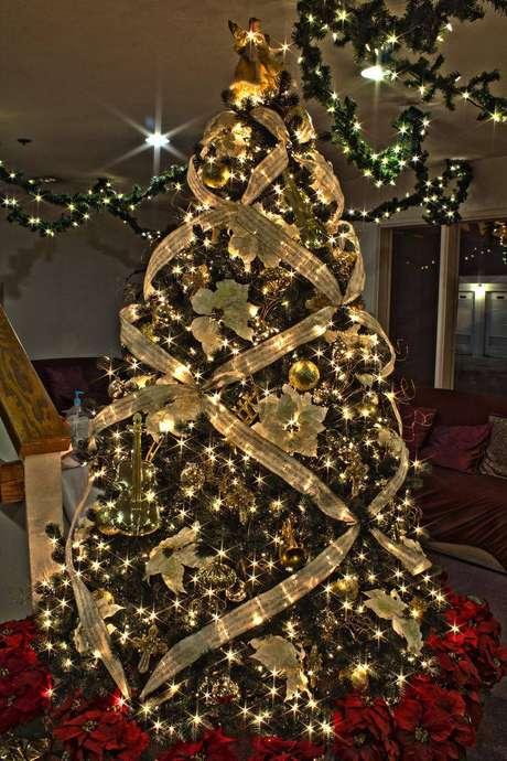 33. Árvore de natal com decoração de fitas, flores e bolinhas douradas
