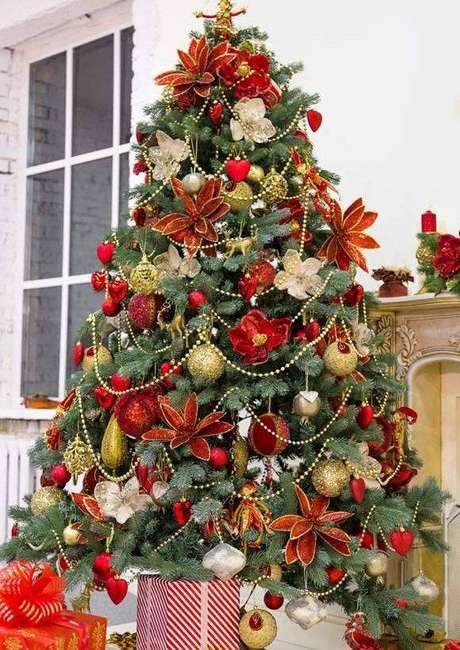 27. Árvore de natal decorada com enfeites vermelhos marcantes e detalhes de dourado