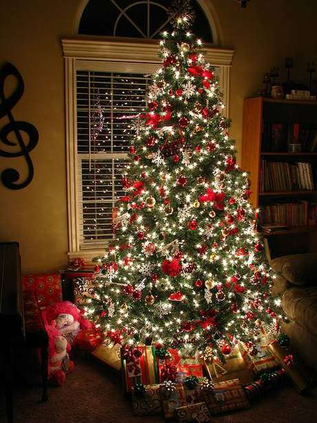 28. Árvore natalina com enfeites vermelhos e pisca-pisca aceso