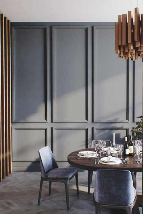 23. Sala de jantar moderna decorada com pendente de madeira sobre a mesa e boiserie pintado de cinza – Foto: Mauricio Gebara Arquitetura