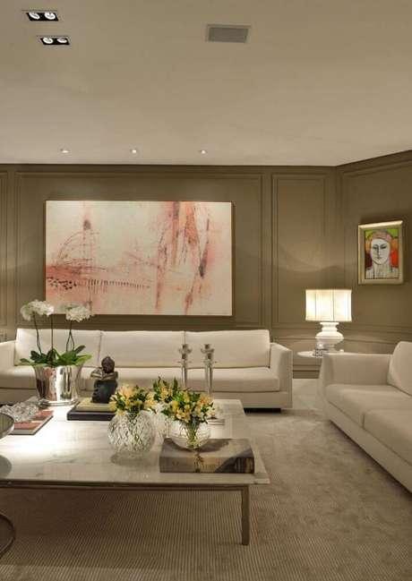 27. Decoração clássica em tons neutros para sala com sofá branco e moldura de parede – Foto: Marlon Gama