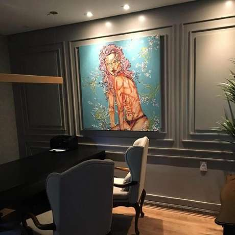 39. Decoração moderna para escritório com boiserie pintado de cinza e com grande quadro – Foto: Dayane Moreschi