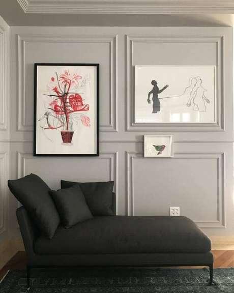 41. Decoração para ambiente com divã preto e quadros na parede sobre boiserie – Foto: Nelson Kabarite