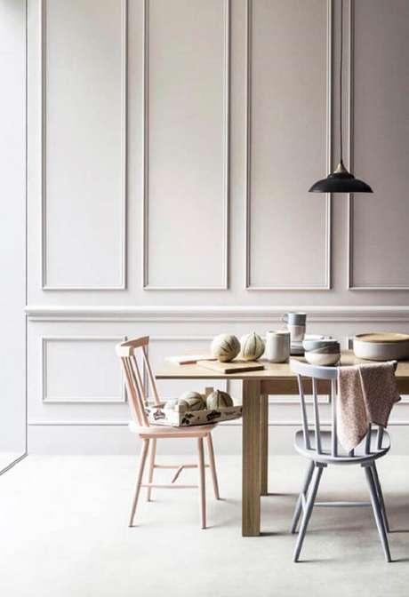 9. Decoração minimalista para sala de jantar com pendente preto sobre mesa de madeira e parede de boiserie – Foto: Pinterest