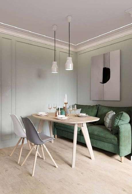 54. Moldura de parede para sala com sofá verde e mesa de madeira – Foto: Pinterest