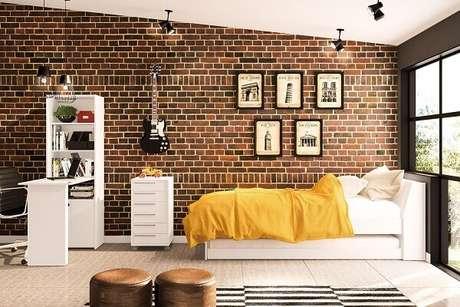 1- Decorando quarto para jovens você pode utilizar parede de tijolinhos, quadros e instrumento musical na decoração. Imagem: Politorno