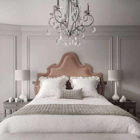 56. Decoração clássica para quarto de casal com moldura de parede, cabeceira rosé e lustre – Foto: Nosso Sobradinho