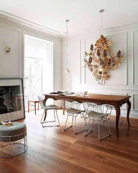 60. Sala de jantar decorada com moldura de parede e mesa de madeira com cadeiras modernas – Foto: Pinterest