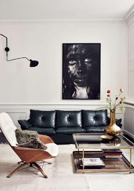 63. Sala moderna decorada com boiserie grande e quadro sobre o sofá de couro preto – Foto: Main Life Style