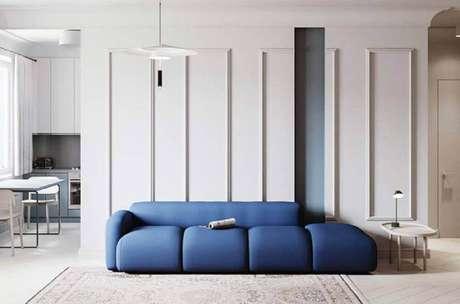 64. Sala de estar moderna decorada com moldura de parede e sofá azul – Foto: Pinterest