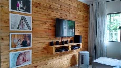 70- A parede de pallet em sala simples tem nichos nos mesmos tons para acomodar aparelhos eletrônicos. Fonte: Pinterest