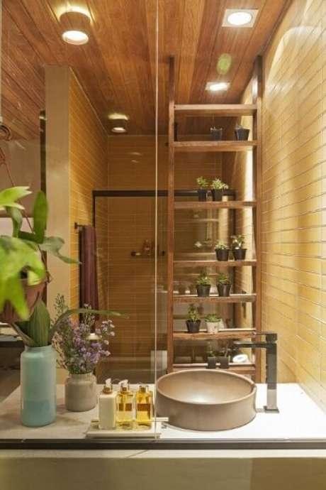 37. Banheiro com plantas em estante vazada de madeira. Projeto de Isabela Bethonico