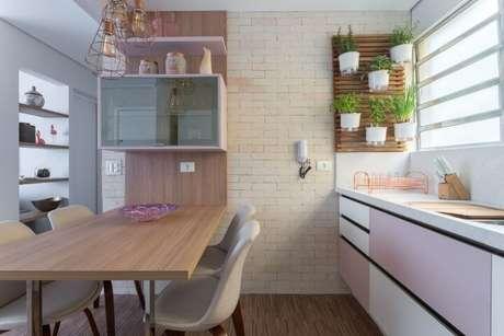 24. Cozinha americana com jardim em treliça pequena de madeira. Projeto de Márcia Addor