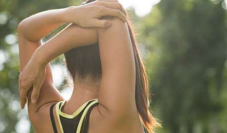 PARA OS TRÍCEPS: com as costas retas, coloque um dos braços atrás da cabeça e segure o cotovelo com a outra mão. Depois repita o movimento com o outro braço