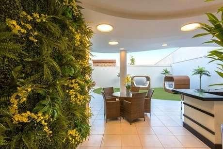 34. Quintal com jardim vertical com flores amarelas. Projeto de Iara Kilaris