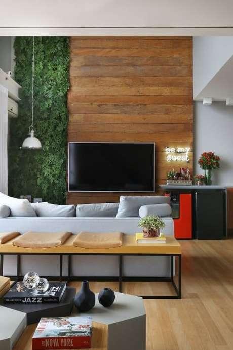 9. Sala de estar com pé direito alto com jardim vertical e painel de madeira. Projeto de Estúdio AE
