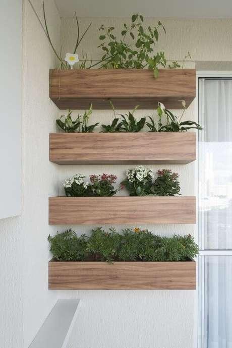 20. Varanda com jardim vertical em cachepots de madeira. Projeto de SP Estúdio