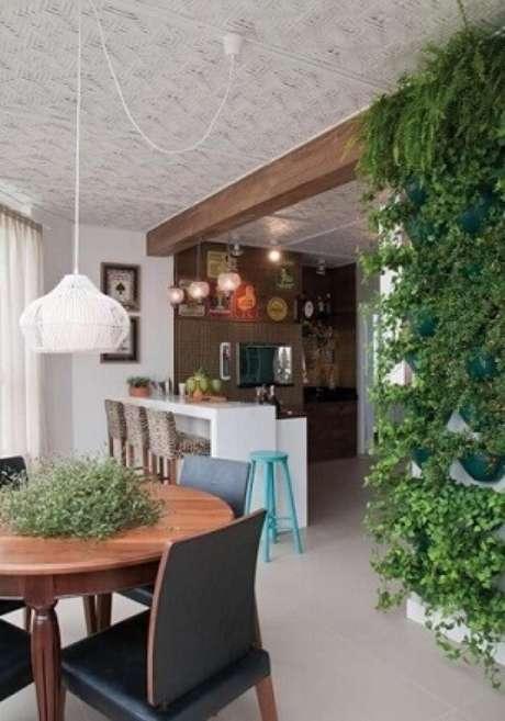 52. Varanda gourmet com jardim vertical em vasos presos direto à parede. Projeto de Hall Arquitetura