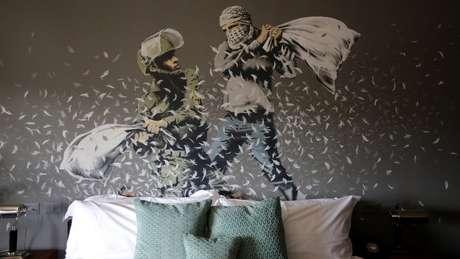 Soldado israelense e militante palestino fazem luta de travesseiro em pintura de Banksy em um hotel criado por ele na Cisjordânia em 2017