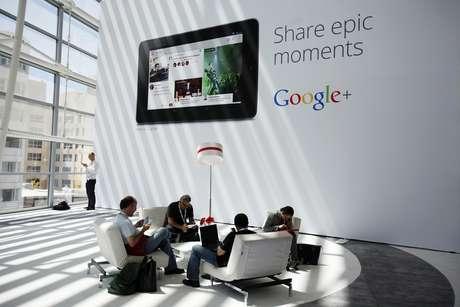 Pessoas sentadas em frente a anúncio do Google+ durante evento da empresa em São Francisco, Estados Unidos 28/06/2012 REUTERS/Stephen Lam